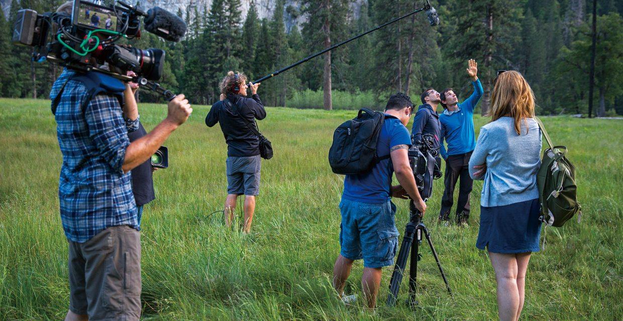 Alex Honnold being interviewed in El Capitan Meadow after free soloing Freerider. Clair Popkin and Jim Hurst document for the Free Solo documentary. Image by Samuel Crossley.
