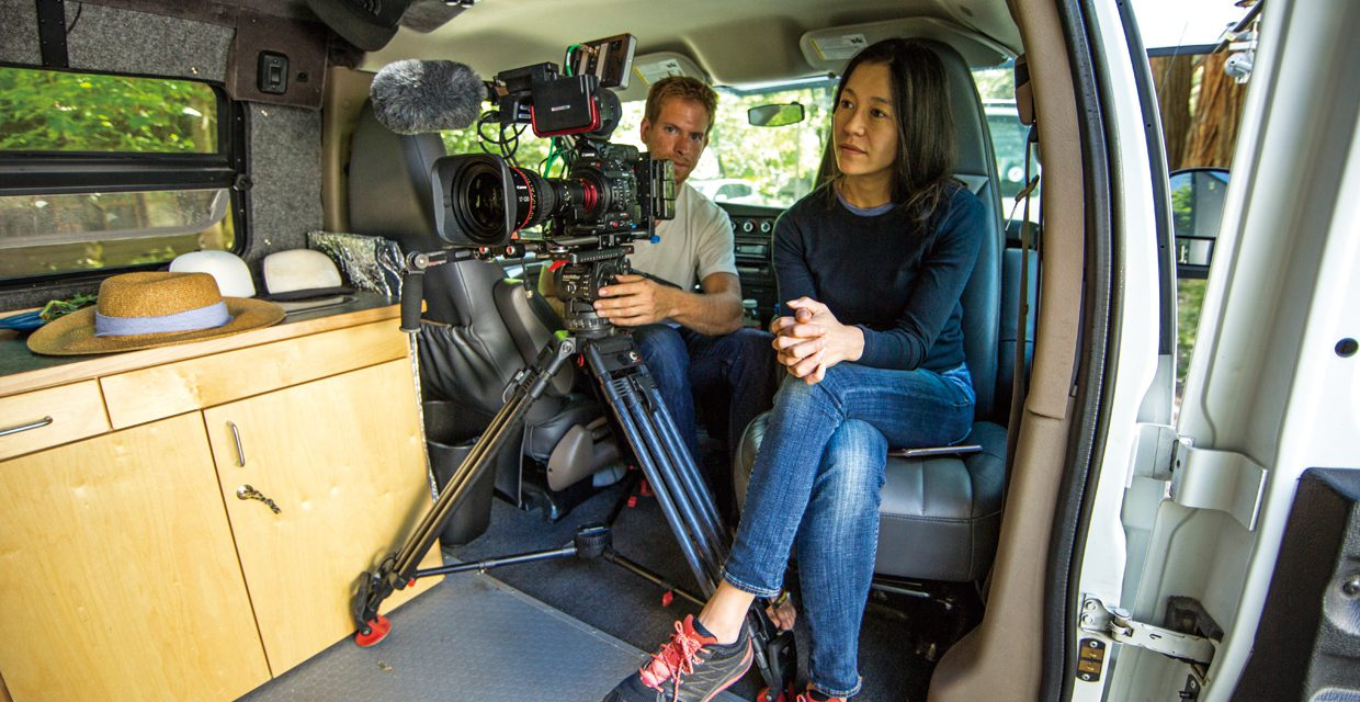 Elizabeth Chai Vasarhelyi Chin prepares to interview Jimmy Chin as Clair Popkin frames up the shot. They are in Jimmy's van in Yosemite.